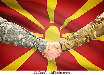 Men in uniform shaking hands with flag on background - Macedonia