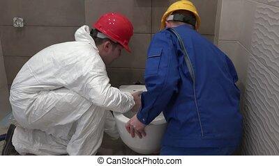 men in work wear hanging wc toilet bowl in new bathroom. Static shot. 4K UHD