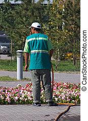 Men irrigate flowerbed