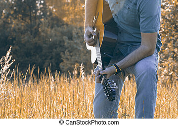 Men is playing on th guitar in nature