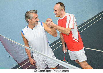 Men joking on badminton court