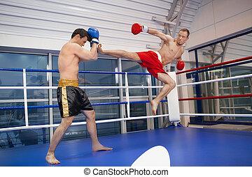 Men kickboxing. Two confident men kickboxing on the ring