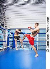Men kickboxing. Two men kickboxing on the ring