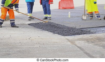 Men lay asphalt on the road. Road re-construction.
