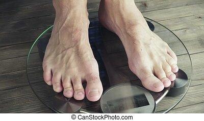 Men legs approaching to weighing digital instrument