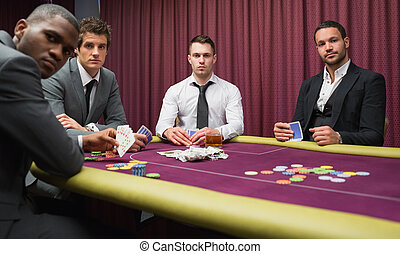 Men looking up from high stakes poker game