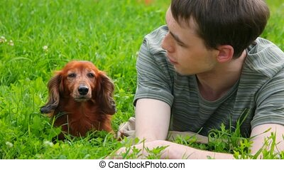 men lying on green grass talking with dog
