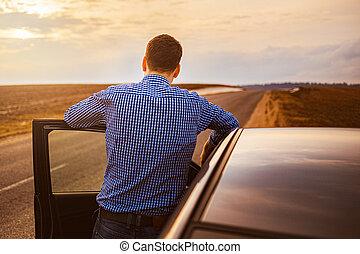 Men near the car at sunset