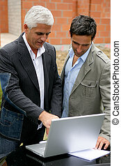 Men on a building site with a laptop