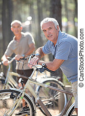 Men on bikes in a forest