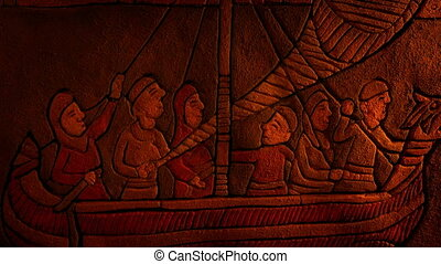 Wall relief carving of boat with men sailing in firelight