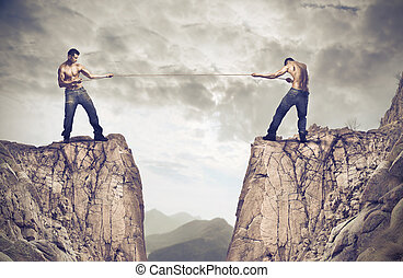 Men on cliff pulling rope - 2 men standing on cliffs and...
