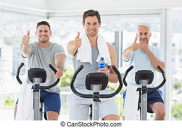 Men on exercise bikes gesturing thumbs up