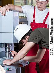 Men operating factory machine