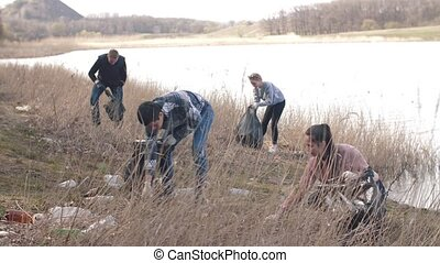 Men picking up trash on the beach