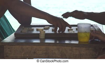 Men playing backgammon and drinking beer from mug on seashore in shadow. Men playing backgammon board with beer glass on blue sea landscape.