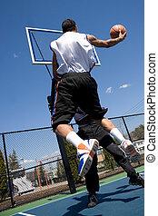 Men Playing Basketball - A young basketball player driving...
