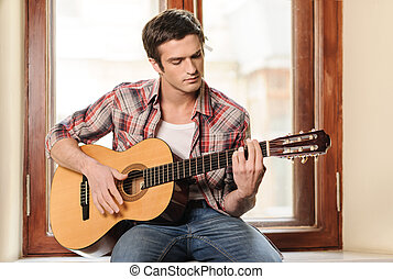 Men playing guitar. Handsome young man sitting on the windowsill and playing acoustic guitar