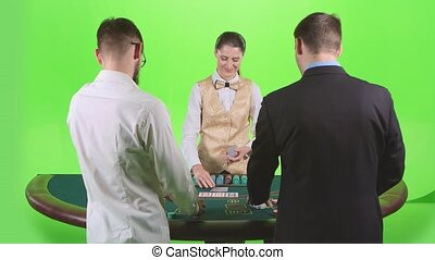 Men playing poker at the table, the dealer deals the cards and the chips. Green screen. Slow motion