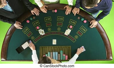 Men playing poker at the table, the dealer deals the cards and the chips. Green screen. Top view