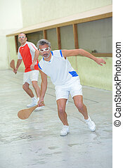 Men playing sport with wooden rackets