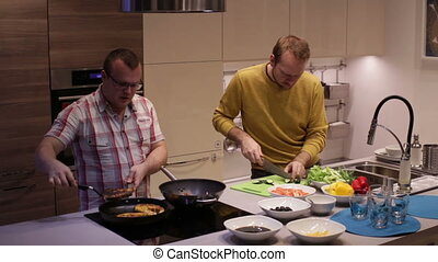 Men preparing food in the kitchen and talking