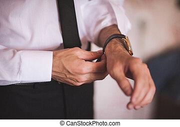 men putting on hand watch wearing shirt