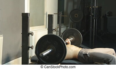 Men raises barbell on exerciser in gym