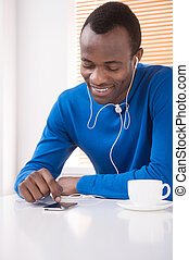 Men relaxing. Cheerful African descent men listening to the...