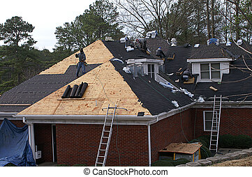 Many men working on roofing a large house