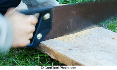 Men saws a piece of wood with hand-held old iron saw close up view