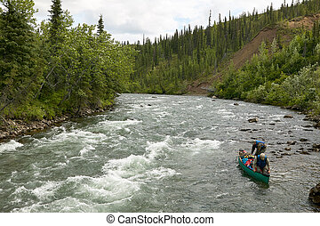 Men setting off on canoe rapid adventure in Alaska
