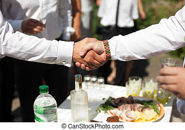Men shake their hands over a dinner table