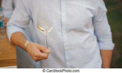Men shakes white wine in a transparent wineglass. A man tasting a glass of white wine.