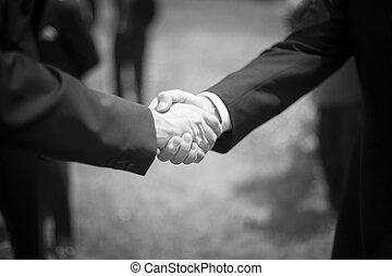 Men shaking hands in wedding reception party