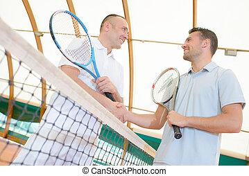 Men shaking hands over the tennis court net