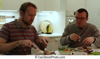 Men sitting at a table eating chicken