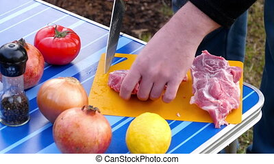 Men slicing meat for BBQ - Slicing meat fo BBQ