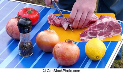 Men slicing meat for BBQ - Slicing meat for holiday BBQ
