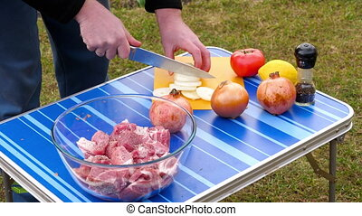 Men slicing onion for BBQ - Men Slicing onion for BBQ, close...