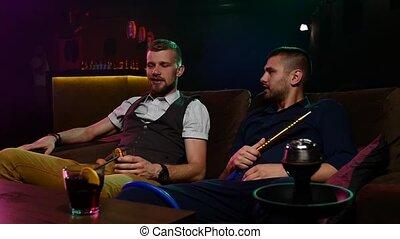 men smoke from shisha pipei n the lounge caffee. Slow motion