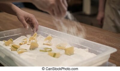 Men sprinkling tortellini with flower and putting them in a...
