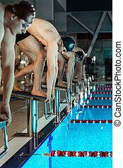 Men standing on starting blocks preparing to begin swimming...