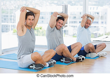 Men stretching on mats in fitness c
