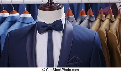 Men suits and Jackets hanging in a clothing store.
