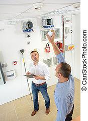 Men testing smoke detectors