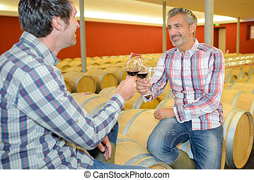 Men toasting red wine, sat on barrels