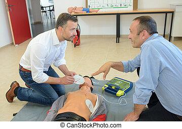 Men training to use defibrillator