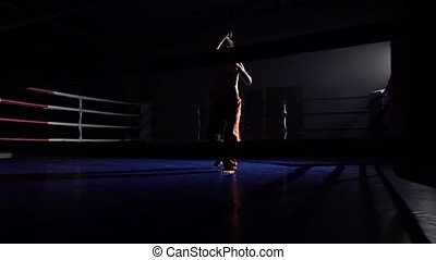 Men trains in the ring, the dark space is lit by a...