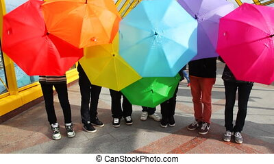 men twist colored umbrellas on bridge